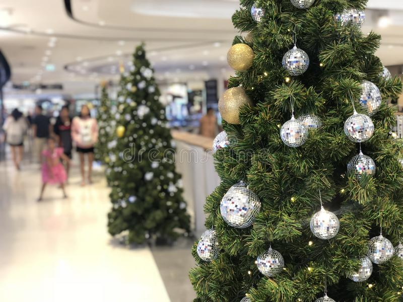 Beautiful Xmas tree decorated with silver and gold sparkling ball in the department. Beautiful christmas tree decorated with silver and gold sparkling ball in royalty free stock photography