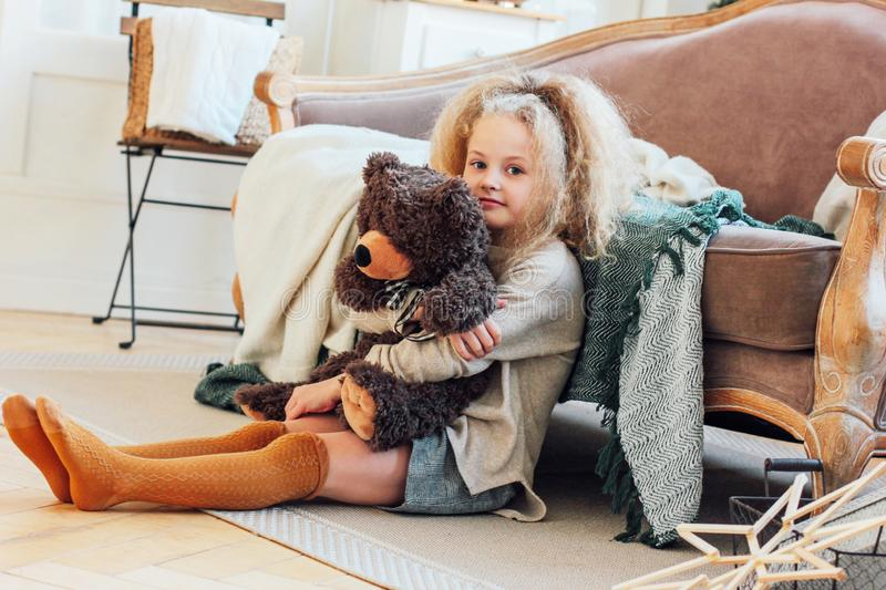 The beautiful 8 year old girl hugs toy bear and looks at the cam. Era. New year Christmas interior royalty free stock photo
