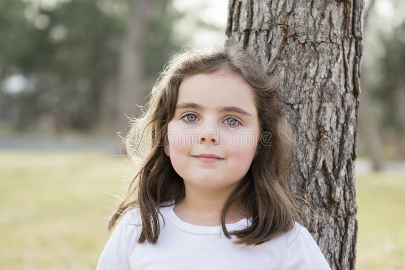 Beautiful 5-year Old Girl Outside on a Fall Day. Standing Beside a Tree in a Park stock images