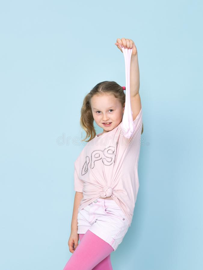 Beautiful 8 year old girl is playing with pink slime in front of blue background stock images
