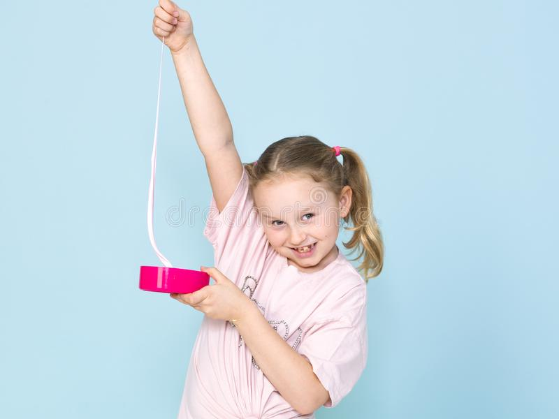 Beautiful 8 year old girl is playing with pink slime in front of blue background stock photos