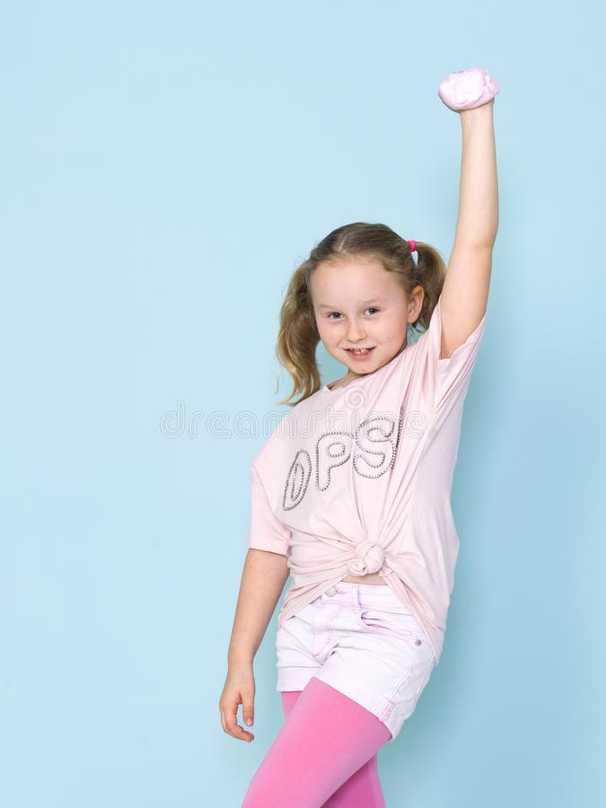 Beautiful 8 year old girl is playing with pink slime in front of blue background royalty free stock photo
