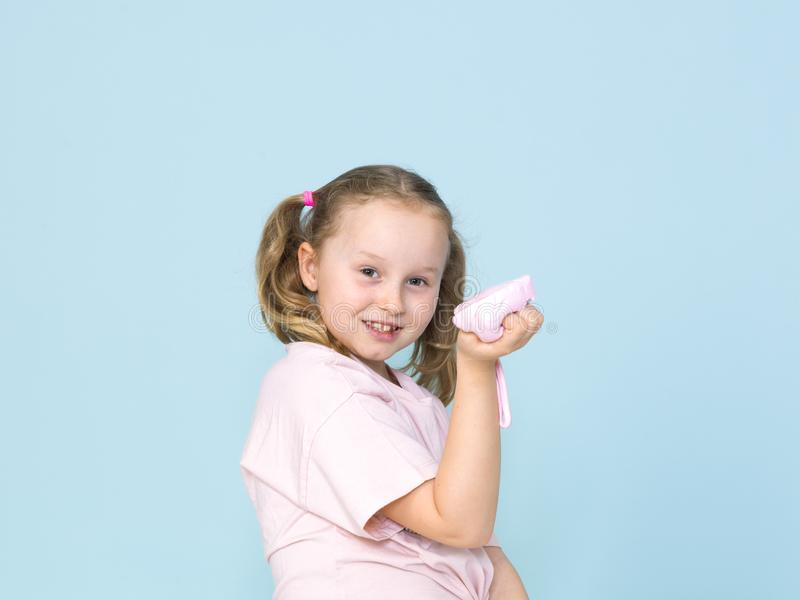 Beautiful 8 year old girl is playing with pink slime in front of blue background. Beautiful and cool 8 year old girl is playing with pink slime in front of blue stock images