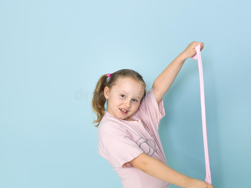 Beautiful 8 year old girl is playing with pink slime in front of blue background royalty free stock photos