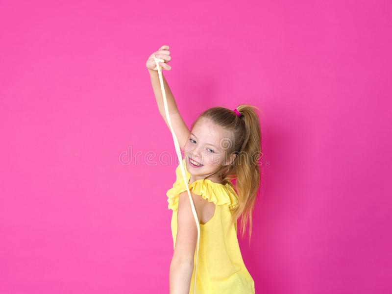 Beautiful 10 year old girl is playing with yellow slime in front of pink background and is happy royalty free stock photography