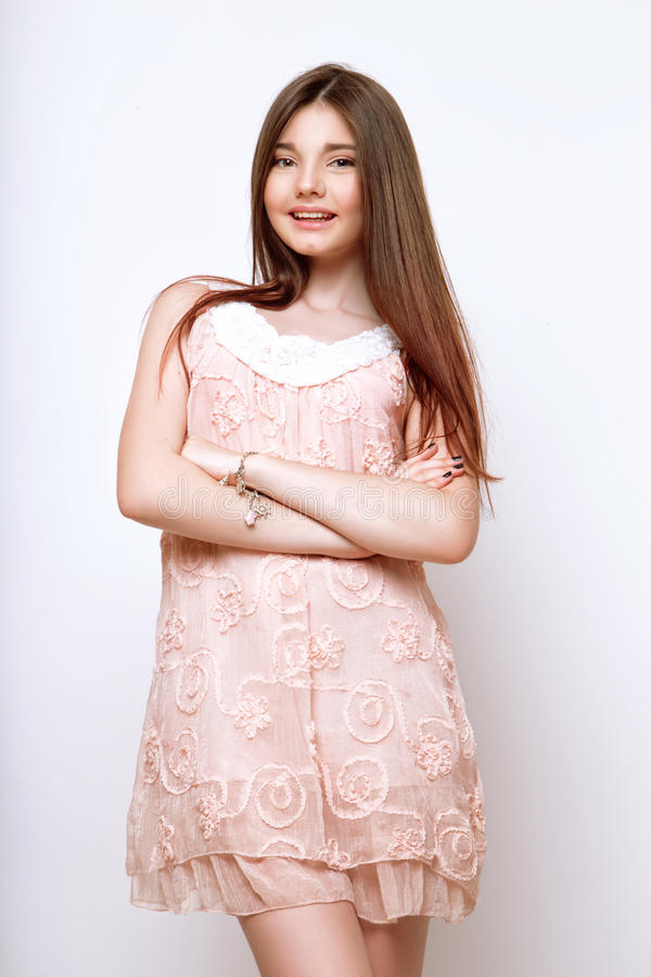 A beautiful 13-years old girl. Dressed in pink dress in studio on white background royalty free stock images