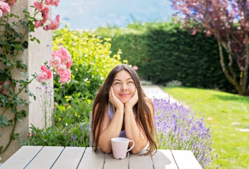 Beautiful 40 years old woman sitting on terrace in blooming summer garden daydreaming enjoying tea. stock image