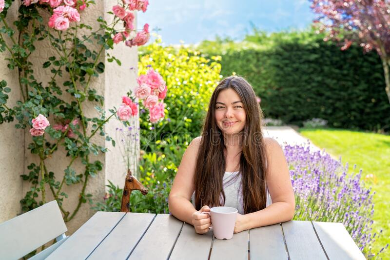 Beautiful 40 years old woman sitting on terrace in blooming summer garden enjoying tea. royalty free stock photography