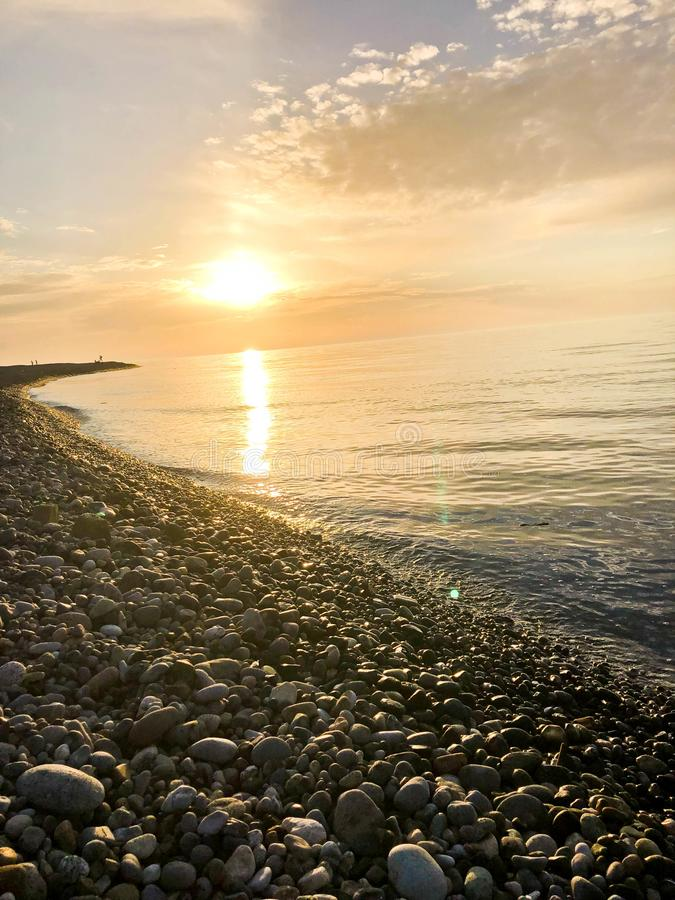 Beautiful yellow bright sunset on the sea, river, lake, pond, water on the rocky beach of a tropical warm resort with round stones royalty free stock images