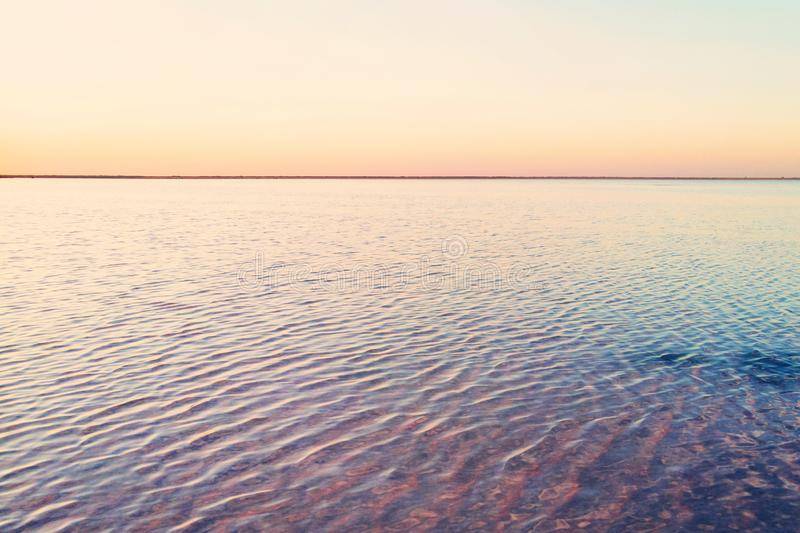Beautiful yellow pink sunset over the lake. The straight line of the horizon. Rose water in a salt lake. royalty free stock images