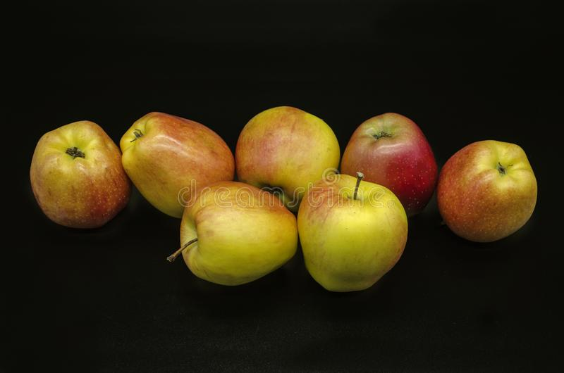 Beautiful yellow with red spots of ripe apples on a black background royalty free stock photography