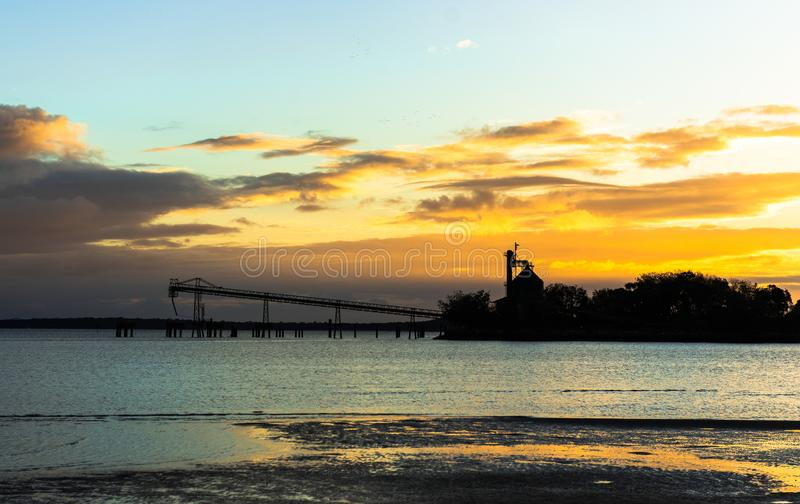 Sunset over small industrial harbour royalty free stock images