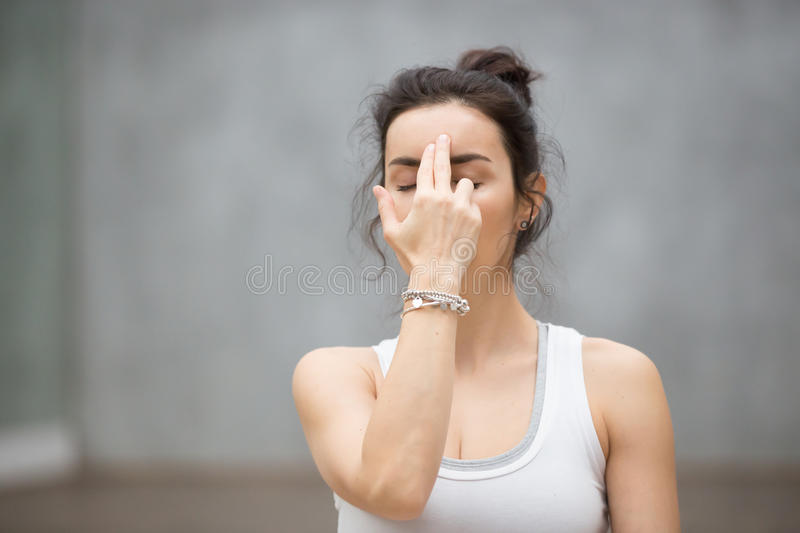 Beautiful Yoga: Alternate Nostril Breathing. Front view portrait of beautiful young woman wearing white tank top working out against grey wall, resting after stock image