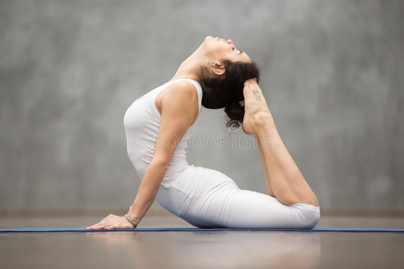 Beautiful Yoga: Royal Cobra Pose. Side view portrait of beautiful young woman with tattoo on her foot meaning Wild kitty working out against grey wall, doing stock photography