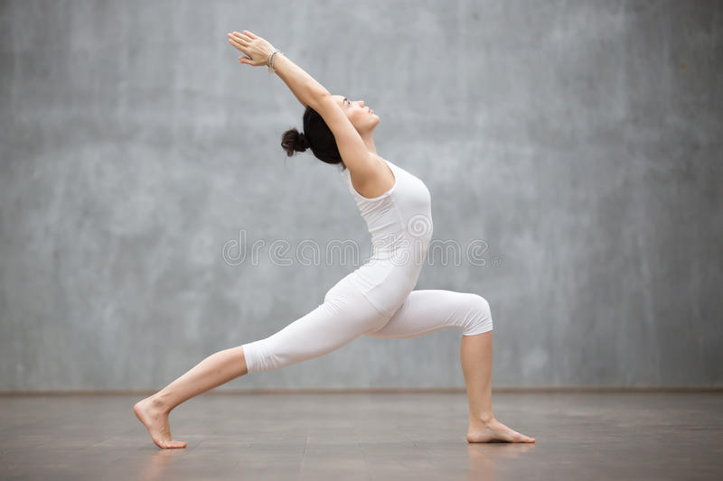 Beautiful Yoga: Warrior one pose. Side view portrait of beautiful young woman wearing white tank top working out against grey wall, doing yoga or pilates royalty free stock image