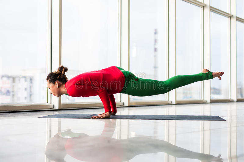 Beautiful yoga woman practice in a big window hall background. Yoga concept royalty free stock photo