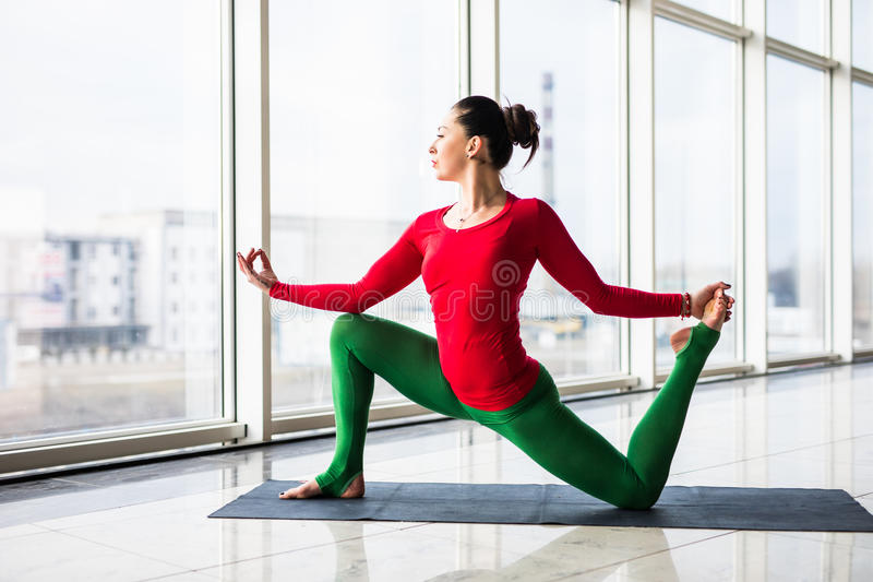Beautiful yoga woman practice in a big window hall background. Yoga concept royalty free stock images
