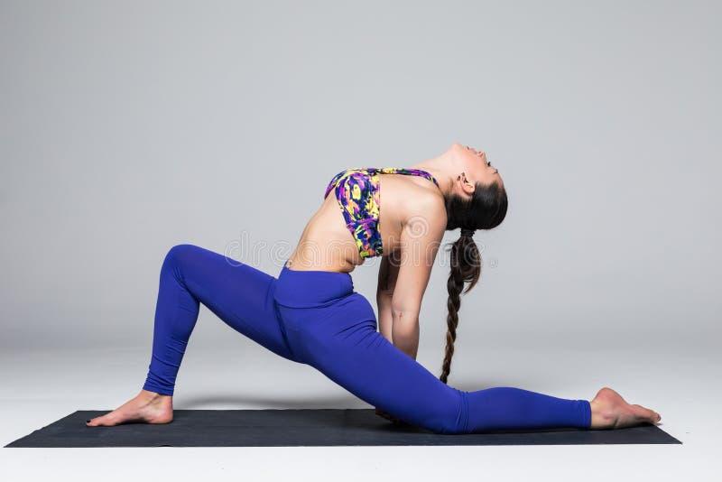 Beautiful yoga woman practice yoga poses on grey background. Anjanejasana. Beautiful yoga woman practice yoga poses on grey background. Yoga concept royalty free stock photos