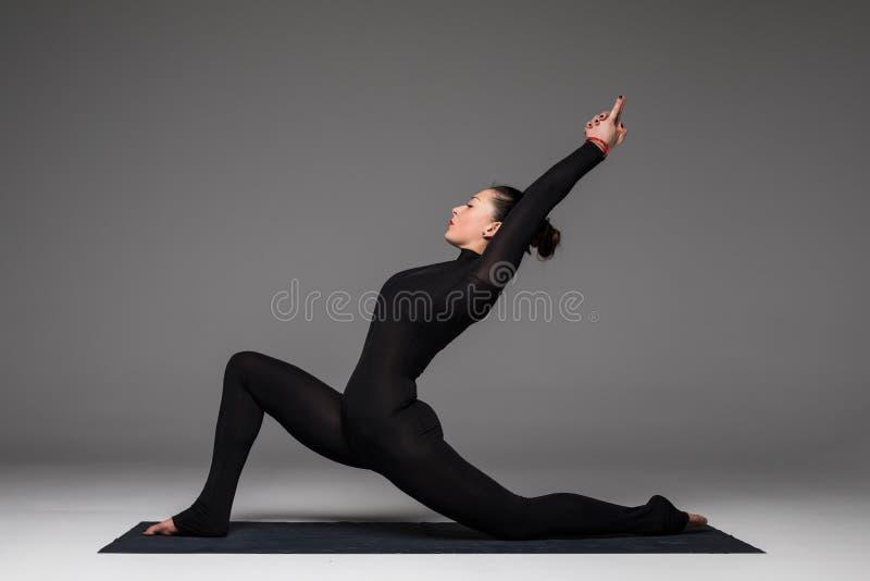 Beautiful yoga woman practice yoga poses on grey background. Anjaneyasana. Beautiful yoga woman practice yoga poses on grey background. Yoga concept royalty free stock photo
