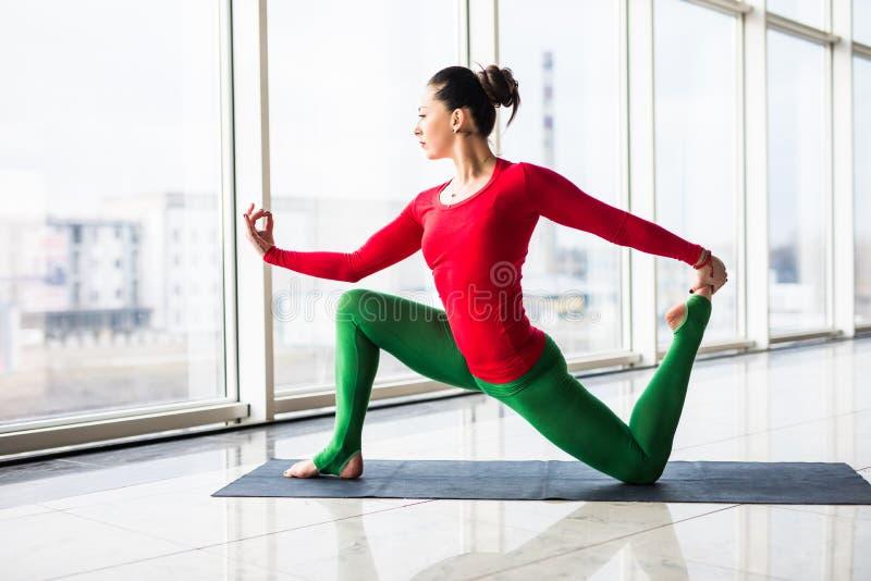 Beautiful yoga woman practice yoga poses on grey background. Beautiful yoga woman practice in a big window hall background. Yoga concept royalty free stock image