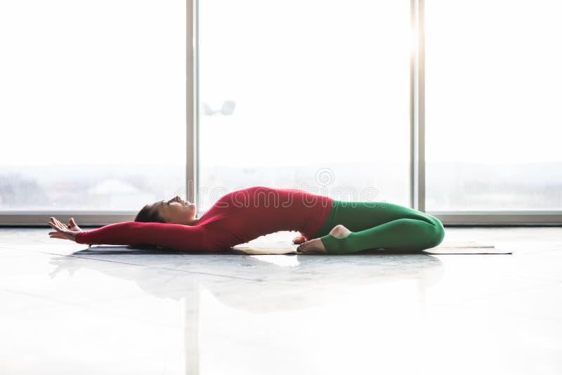 Beautiful yoga woman practice yoga poses on grey background. Beautiful yoga woman practice in a big window hall background. Yoga concept royalty free stock photography