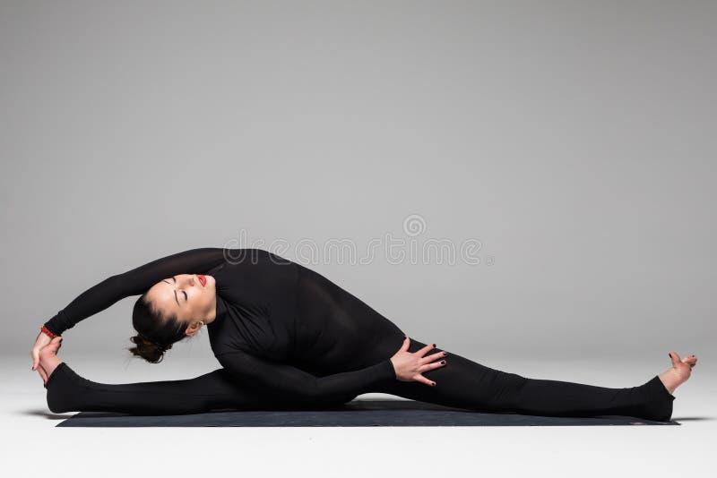 Beautiful yoga woman practice yoga poses on grey background. Yoga concept royalty free stock photo