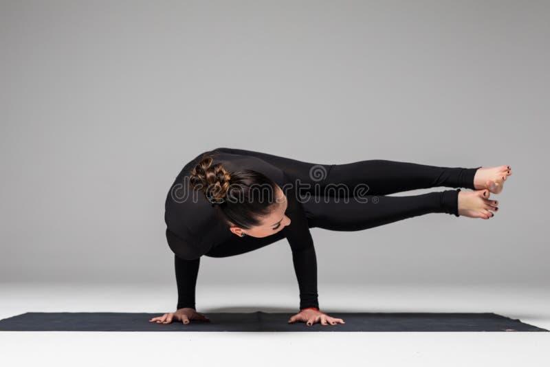 Beautiful yoga woman practice yoga poses on grey background. Yoga concept stock photo