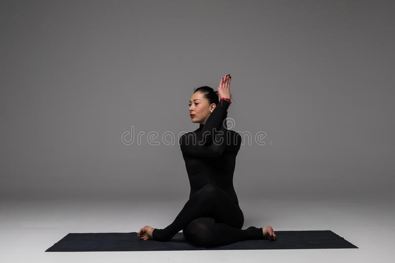 Beautiful yoga woman practice yoga poses on grey background. stock photography