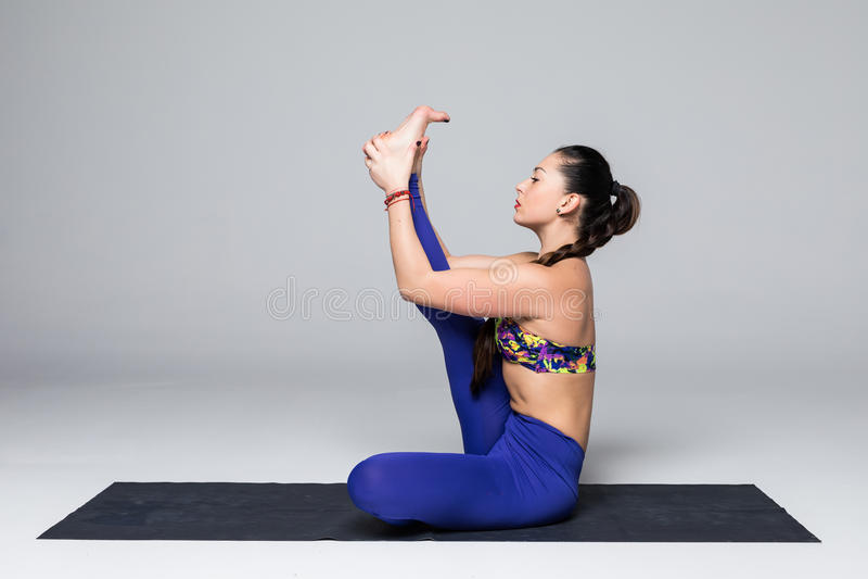 Beautiful yoga woman practice yoga poses on grey background. stock image