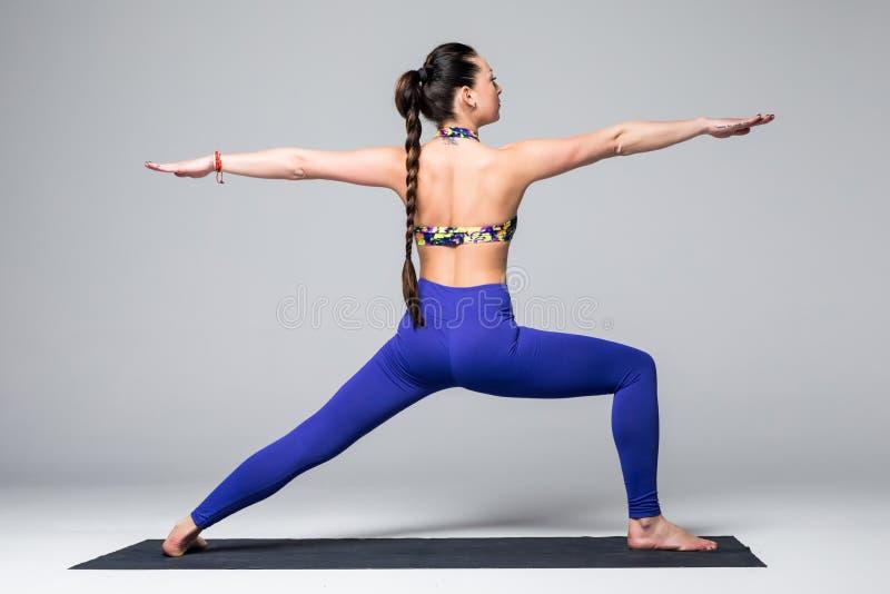 Beautiful yoga woman practice yoga poses on grey background. Yoga concept royalty free stock image