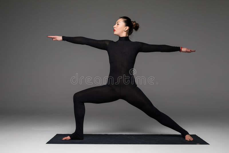 Beautiful yoga woman practice yoga poses on grey background. royalty free stock photography