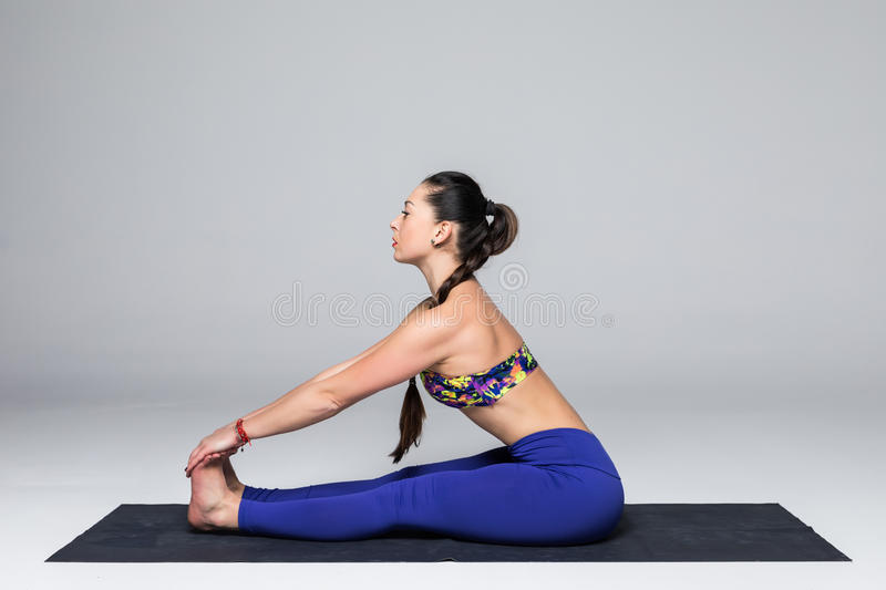 Beautiful yoga woman practice yoga poses on grey background. royalty free stock image