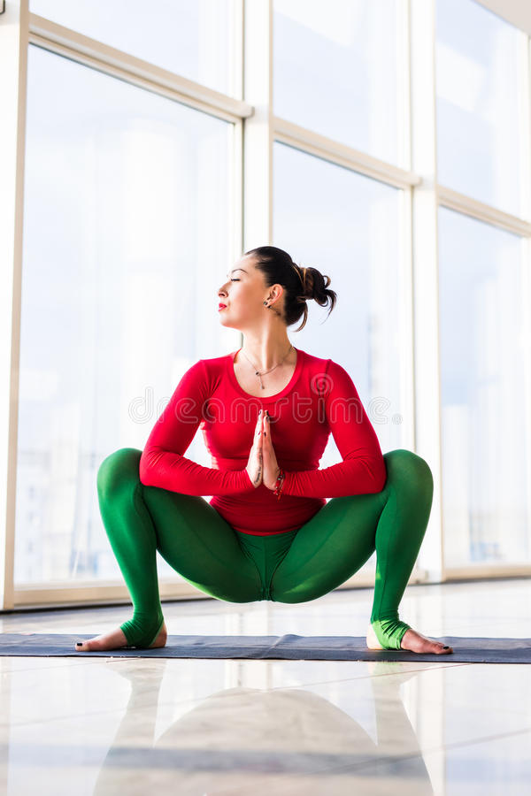 Beautiful yoga woman practice yoga poses on grey background. Kakasana. Beautiful yoga woman practice in a big window hall background. Yoga concept royalty free stock photography