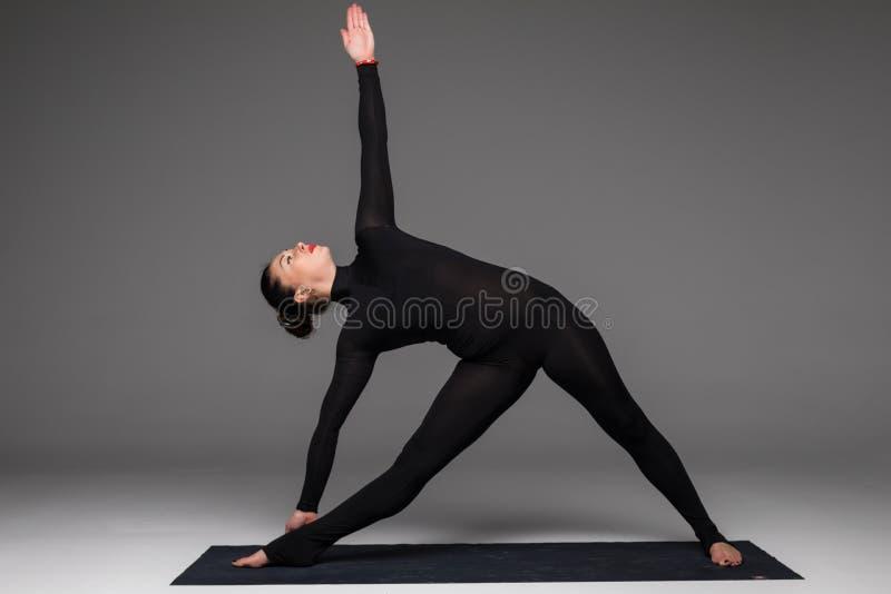 Beautiful yoga woman practice yoga poses on grey background. stock photo