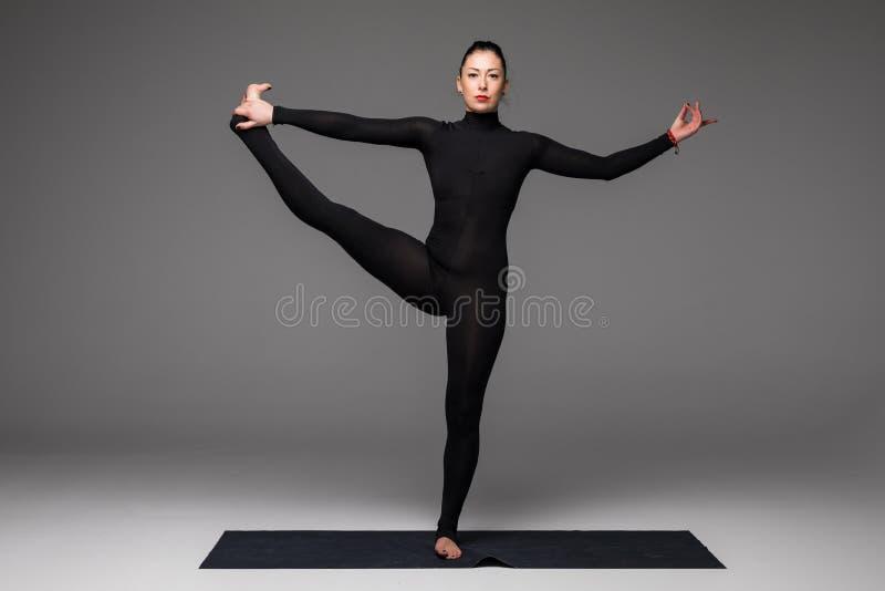 Beautiful yoga woman practice yoga poses on grey background. Utthita hasta. Beautiful yoga woman practice yoga poses on grey background. Yoga concept stock image