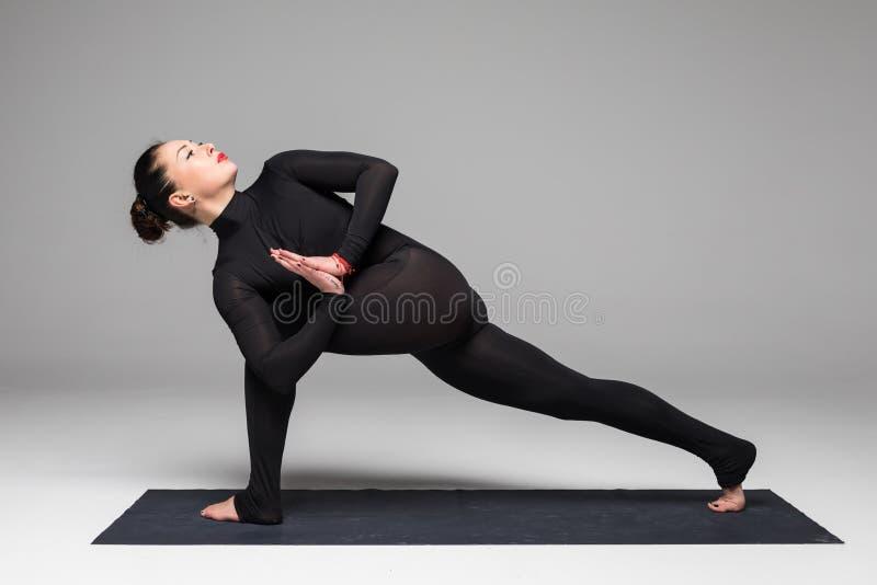 Beautiful yoga woman practice yoga poses on grey background. royalty free stock photos