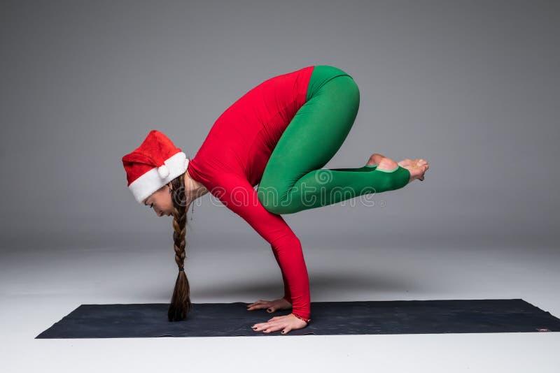 Beautiful yoga woman in santa hat practice yoga poses. On grey background. Yoga concept stock photo