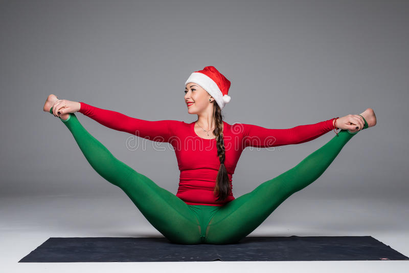 Beautiful yoga woman in santa hat practice yoga poses on grey background. Yoga concept royalty free stock photos