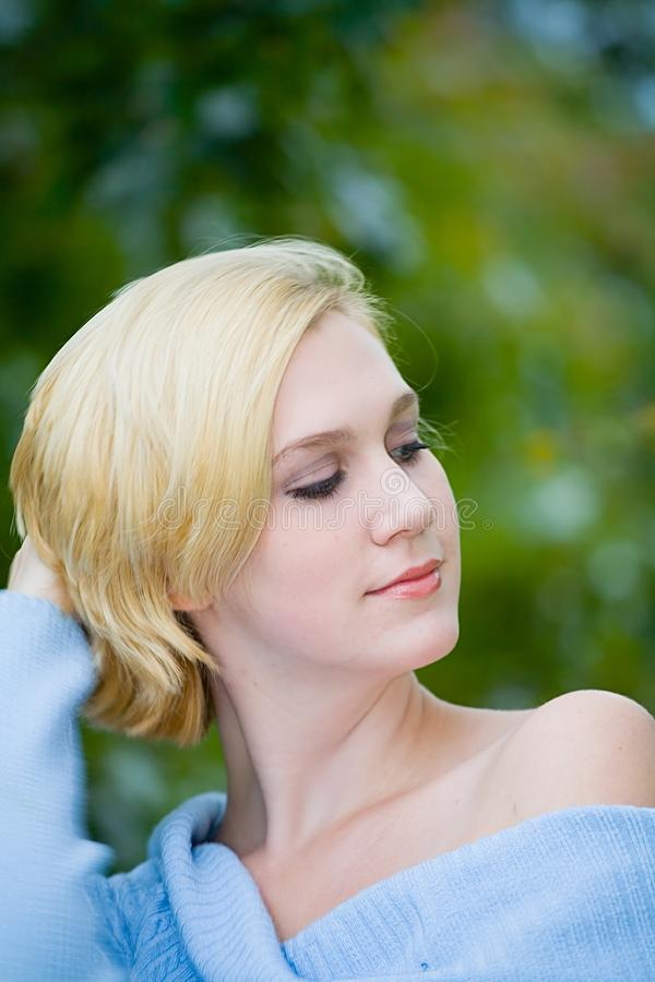 Beautiful Yong Blonde Girl with Blue Eyes Combing her Hair royalty free stock photo