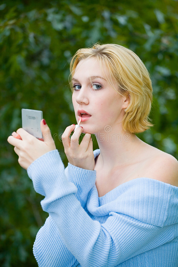 Beautiful Yong Blonde Girl with Blue Eyes Putting on Makeup stock photography