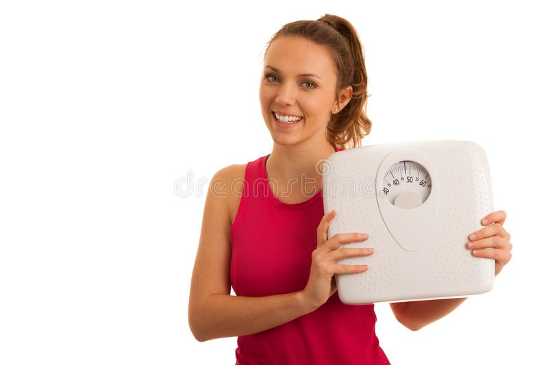 Beautiful young active fit woman hold scale as gesture of loosing weight isolated over white background - weight loss stock image