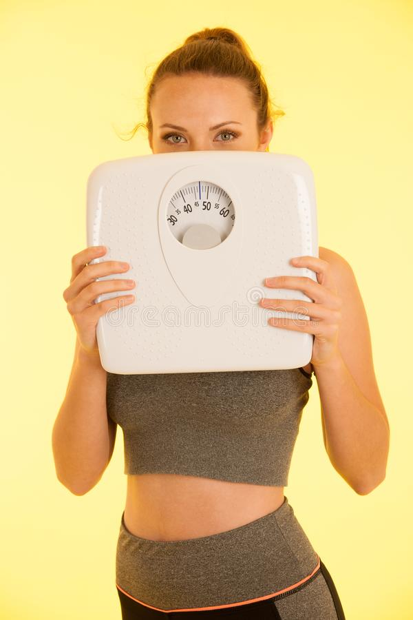 Beautiful young active fit woman hold scale as gesture of loosing weight isolated over white background - weight loss stock photos