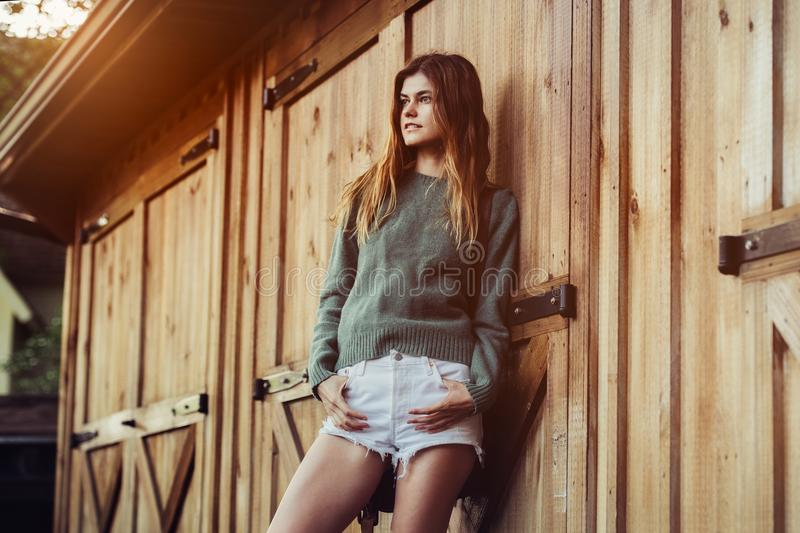 Beautiful young adult country woman posing near barn farm wooden doors at sunset time wearing white shorts and green sweater. royalty free stock image