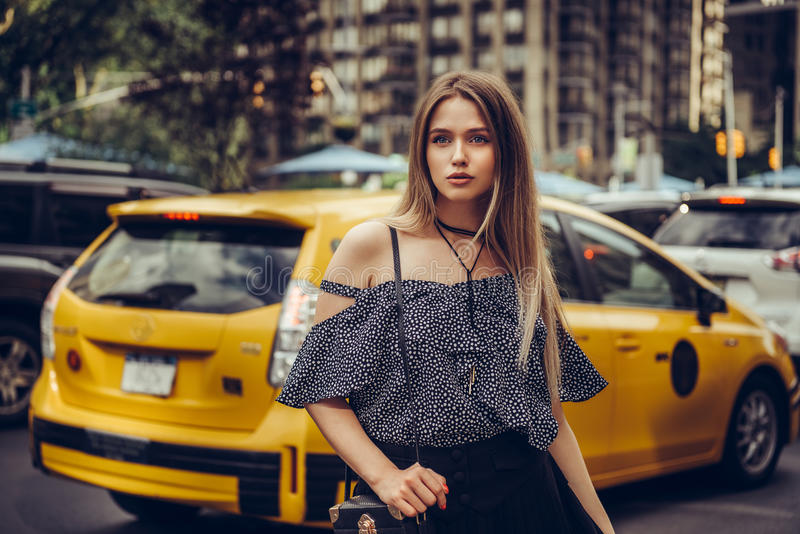 Beautiful young adult elegant woman came out from the taxi and walking in New York City street wearing summer clothes. royalty free stock image