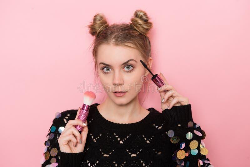 Beautiful young adult woman doing makeup using Mascara and powder brush.  royalty free stock photography