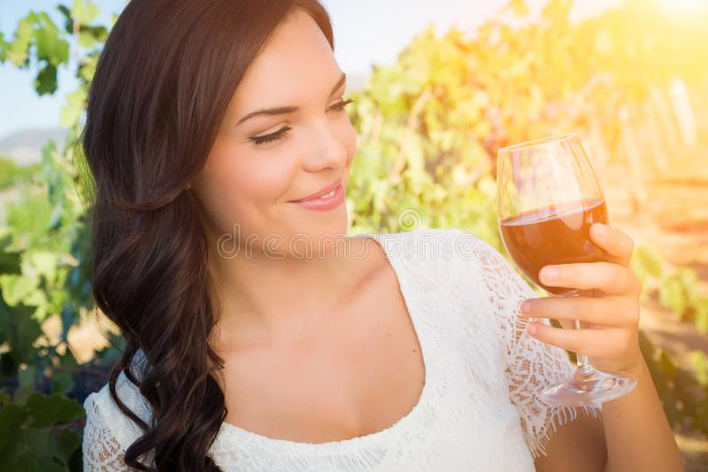 Beautiful Young Adult Woman Enjoying Glass of Wine Tasting In The Vineyard royalty free stock photo