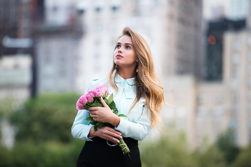 Beautiful young adult woman holding bouquet of pink roses against city background and looking up stock photo