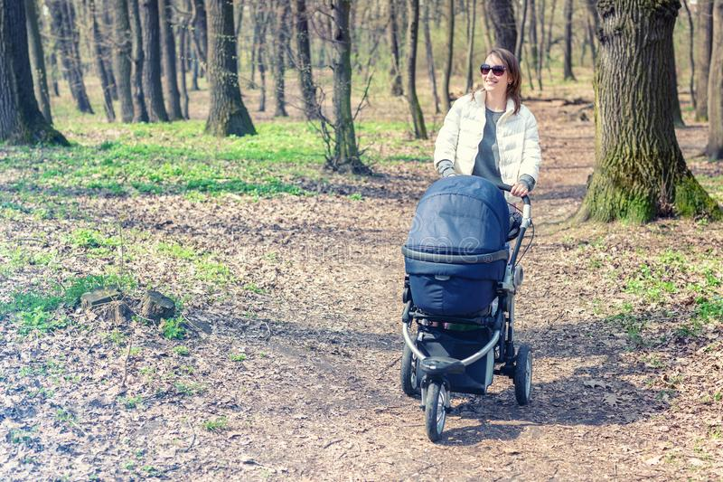 Beautiful young adult woman walking with baby in stroller through forest or park on bright sunny day. Healthy lifestyle royalty free stock photos