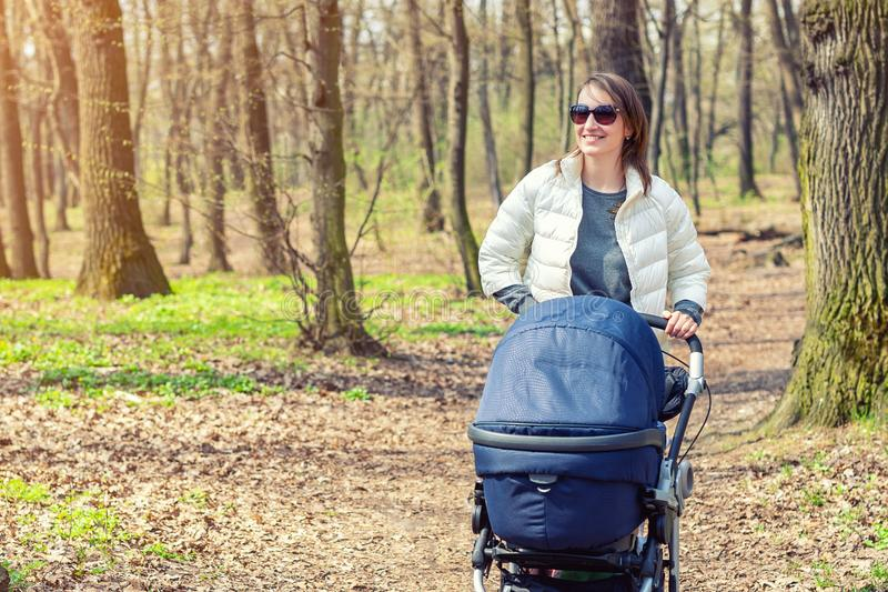 Beautiful young adult woman walking with baby in stroller through forest or park on bright sunny day. Healthy lifestyle royalty free stock images