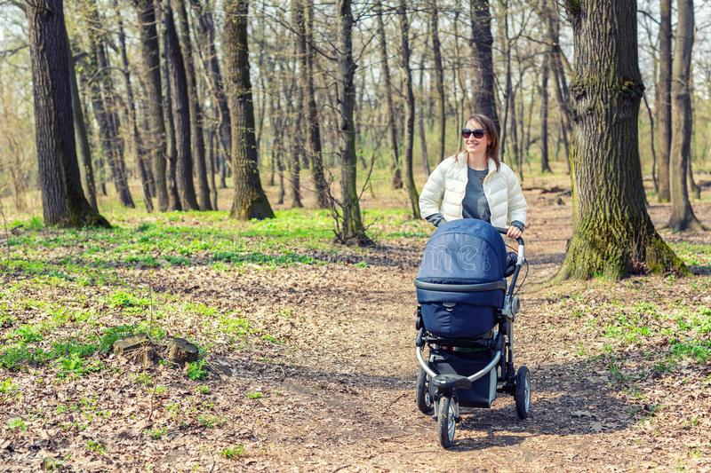 Beautiful young adult woman walking with baby in stroller through forest or park on bright sunny day. Healthy lifestyle royalty free stock image